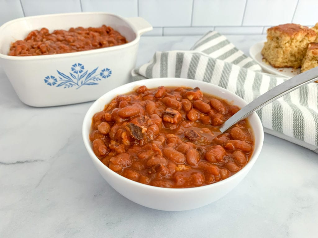 A bowl and pot of brown sugar bacon baked beans with cornbread