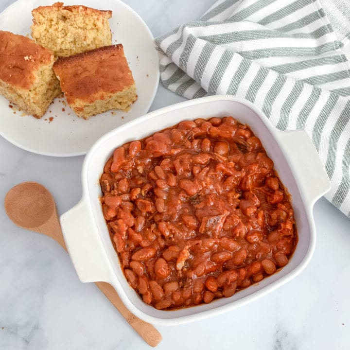 A dish of homemade baked beans with bacon and a side of cornbread