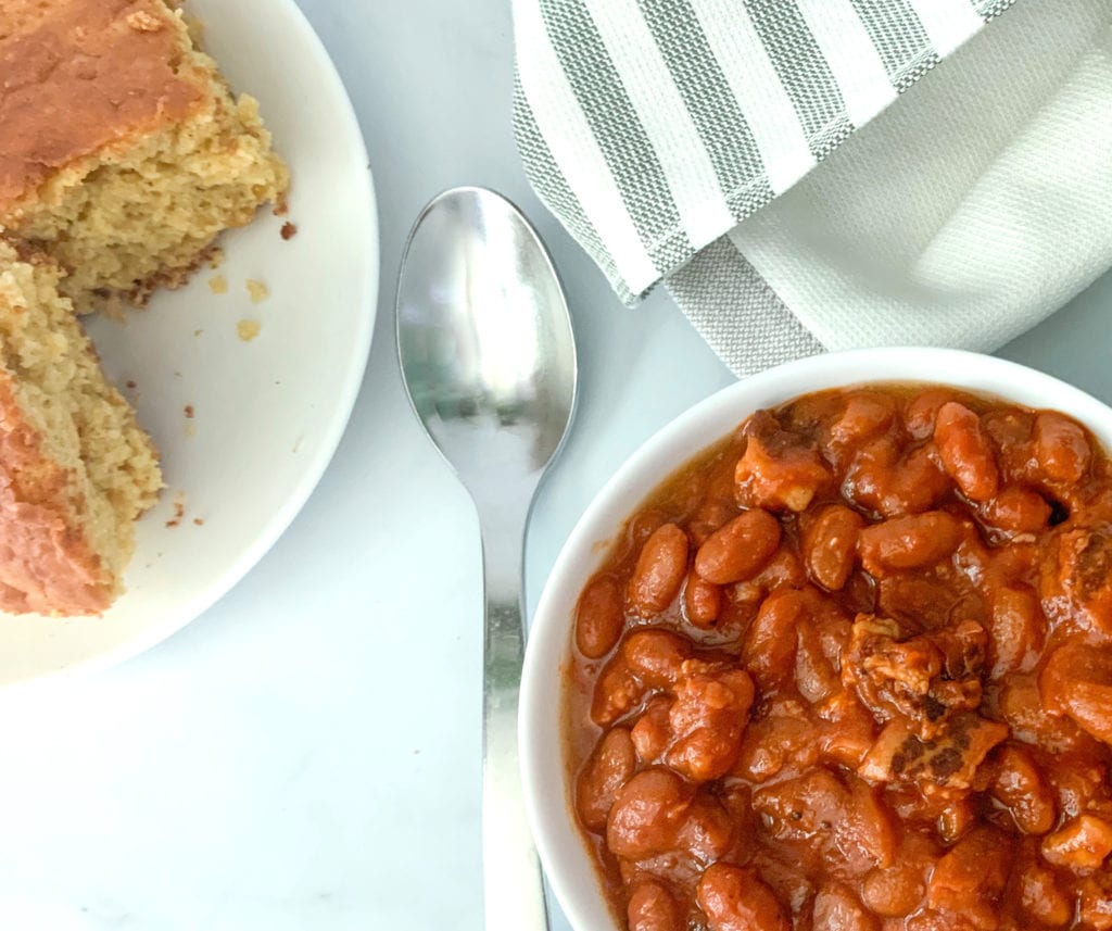 A bowl of perfectly baked beans with bacon and a side for cornbread