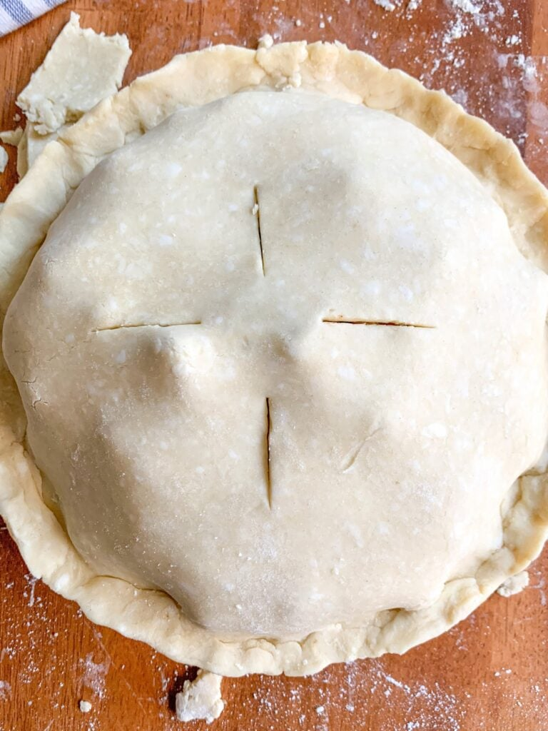 Mom's apple pie recipe from scratch-homemade apple pie filling encased in a buttery flaky crust, ready for the oven.