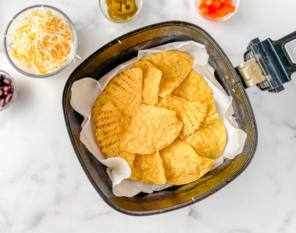 Arrange the tortilla chips in a single layer in the air fryer basket