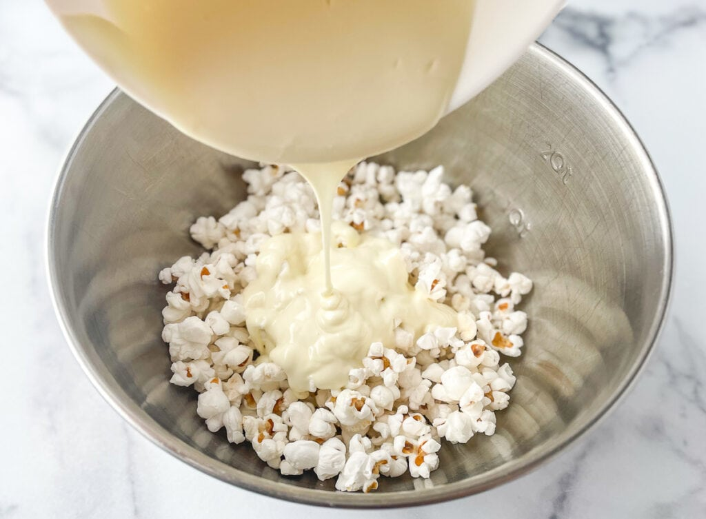 Melted almond bark or white chocolate chips, poured over popped popcorn
