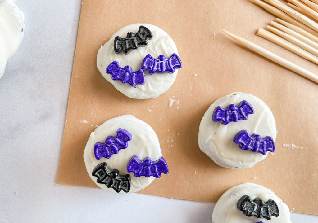 Attaching the bat sprinkles to the melted candy coating