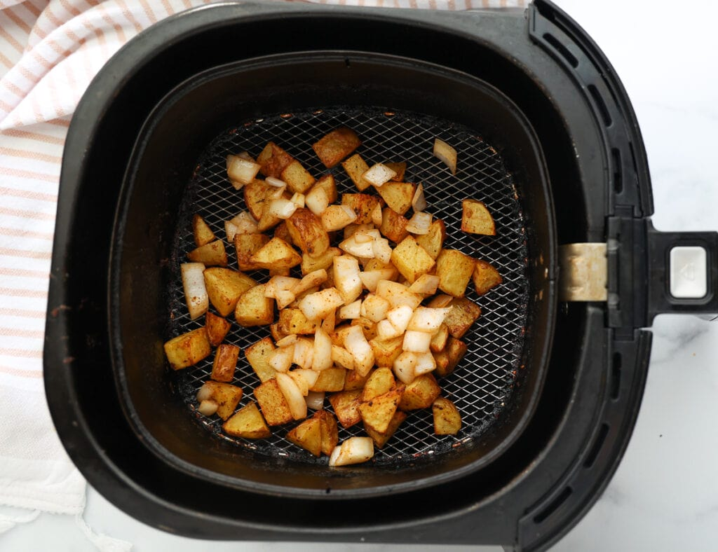 Add seasoned onions to potatoes in the air fryer